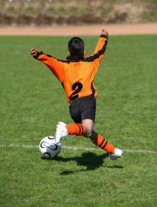 junger Fußballer schwebt mt Ball über den Rasen